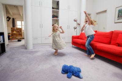 Befestigt der Fachhandwerker Bodenbeläge mit einem wohngesunden und umweltfreundlichen EMICODE EC1 zertifizierten-Klebstoff am Unterboden, können sie nicht mehr schwingen – und somit keine störenden Töne erzeugen. Eltern können ihre wohlverdiente Ruhe genießen, während ihre Kinder im selben Raum unbeschwert spielen. (c) IBK