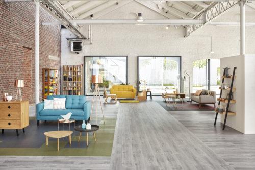 """Kuscheliger Teppichboden in der Sitzecke und ein strapazierfähiger sowie wasserbeständiger """"Designboden"""" im stark belaufenen Bereich: Bei Bodenbelägen können zahlreiche Dekore und Farben immer wieder neu aufeinandertreffen. Jeweils einzigartige Oberflächenbilder entstehen. Achtung: Nur wenn die Beläge auf den Untergrund geklebt werden, lassen sich die Materialien mit fließenden Übergängen und auf einem einheitlichen Niveau verlegen. (c) Tarkett"""